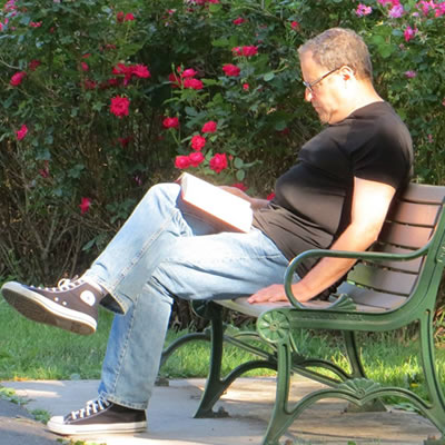 Man sitting on a park bench reading a book