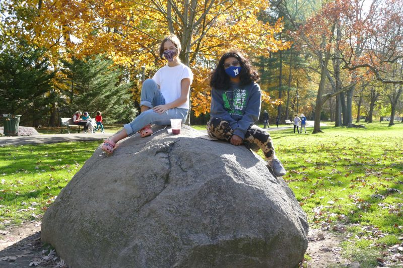 Two Montclair middle school students sitting on a bolder in Anderson Park